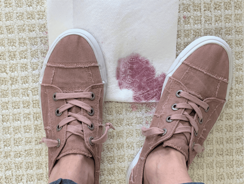 With constant pressure, the red wine stain will begin to transfer to the paper towel or white dish cloth.